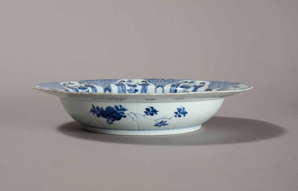 Chinese export blue and white deep bowl, or basin. The central scene of the interior is painted in deep underglaze blue with European court ladies standing on a terrace strewn with flowers, each holding a floral sprig to smell while a servant to one side bears a basket of more flowers. The exterior is decorated with freely painted with floral sprigs.