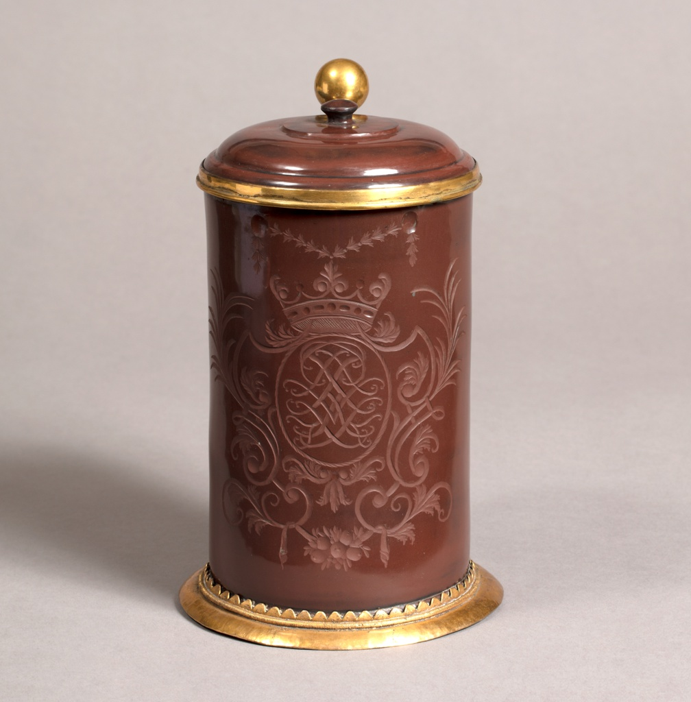 Cylindrical, slightly tapering toward top. Flat domed cover with simple button knob, held by ring mounting and hinge on shoulder of curving flat strap handle. Mount on foot, with triangular tongues holding the base of the tankard. Exterior of tankard, and both surfaces of cover, polished. Tankard engraved on face with interlacing cipher in framework of scrolls, under a crown.