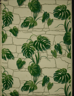 Large-scale design of vining philodendron growing up a flat stone wall. Printed in shades of green and gray on white ground.