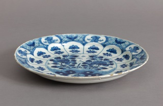 Circular plate painted in underglaze blue on white; center with chinoiserie scene of flowers, rocks, insects; on cavetto with 14 uniform panels with flowers; around rim with evenly-spaced reserves of floral motifs on diaper pattern; bottom, low foot rim, 7 groups of dots painted around rim.