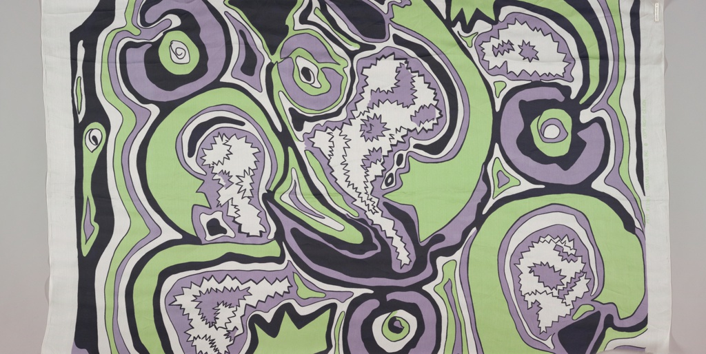 Fragment printed in green, purple and black against white. Pattern of jagged and swirling lines in an allover design.