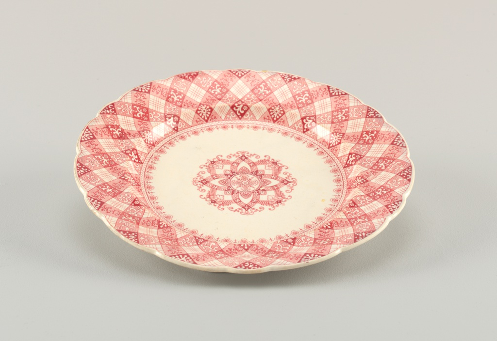 Plate with red transfer print showing floral pattern. Border is lattice with stripes and florals.