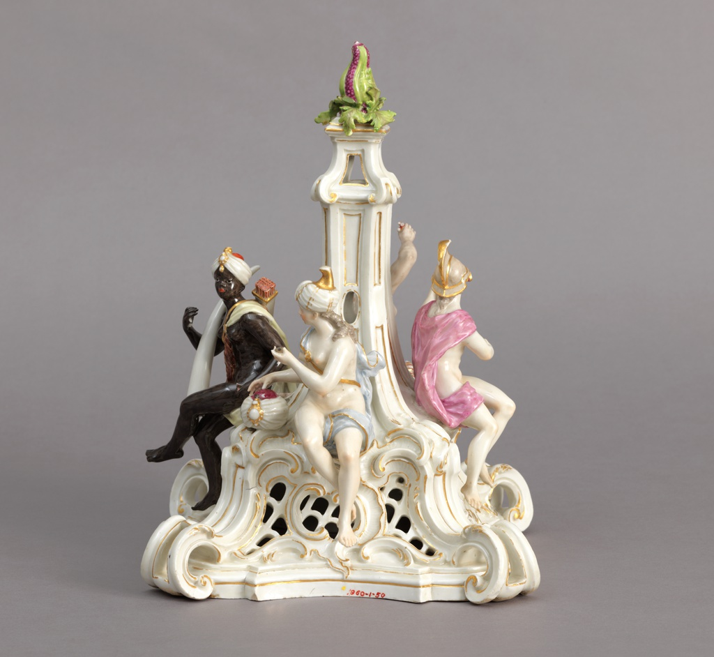 Figures of Asia, Europe, Africa, and America placed on four sides of pierced, scrolled pedestal with fruit finial in center.