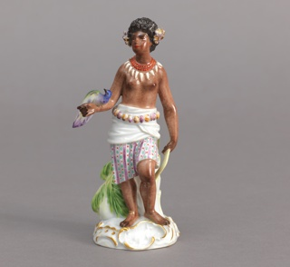 Standing female figure, wearing striped skirt and white overskirt with shell belt. Tan body and curly black hair with flowers on sides; on right arm a bird, in left hand a boomerang. On base, a relief cartouche with kangaroo. Hollow base.