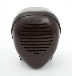 Brown-burgundy ovoid form suggestive of kerchiefed head or kendo mask; horizontal slits for speaker on the front.