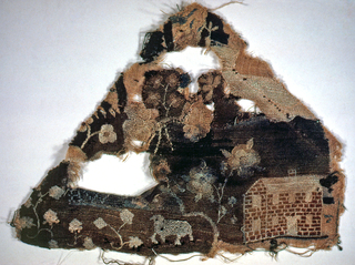 Triangular fragment of  silk embroidered on linen showing sheep and flowers in front of a brick house.