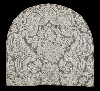 Cap crown with Mechlin ground has a central floral bouquet framed by elaborate symmetrical scrollwork, giving the appearance of a fan, and surrounded by foliated sprays. Made in one piece.