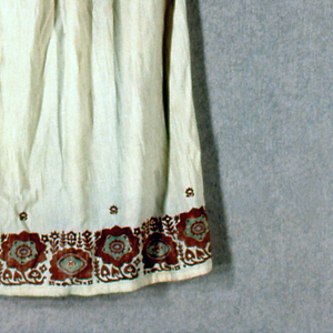 Off-white pullover, long-sleeved tunic style blouse with block printed band of flowers in rust red with green from shoulders to cuffs and around the bottom border. Neck yoke and upper side of cuffs decorated with buttonhole stitches using rust red silk. Neck slit reinforced with a figure-8 stitch using rust red silk. Five white dome-shaped buttons topped by a green glass bead are on each sleeve.