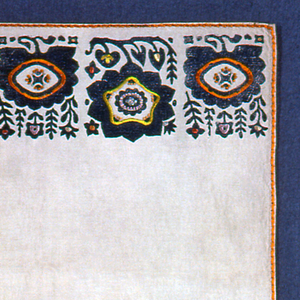 Rectangular panel with a row at both ends of block printed flowers in blue embellished with satin and split stitches and French knots. Sides decorated by orange couching.