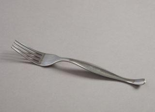 Manufacturer's prototype: four-tined fork with curved contoured handle; matte surface.