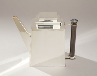 Rectangular, boxy teapot with stepped lid, making form reminiscent of a skyscraper; angular spout; black cylindrical handle; polished surface.