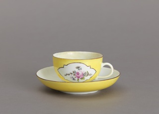 Cup with simple loop handle; saucer deep, with curved sides.  Inside of cup and saucer white, with scattered flowers; outside of cup and underside of rim of saucer yellow, with white reserve panels, on cup, in which are flowers.  Edges of cup and saucer brown.