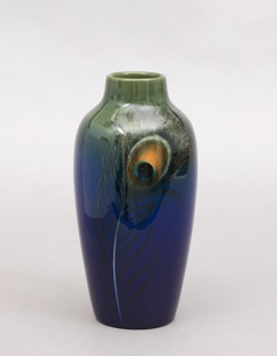 A dark blue and black vase with a larger opening, decorated with one peacock feather on the front.
