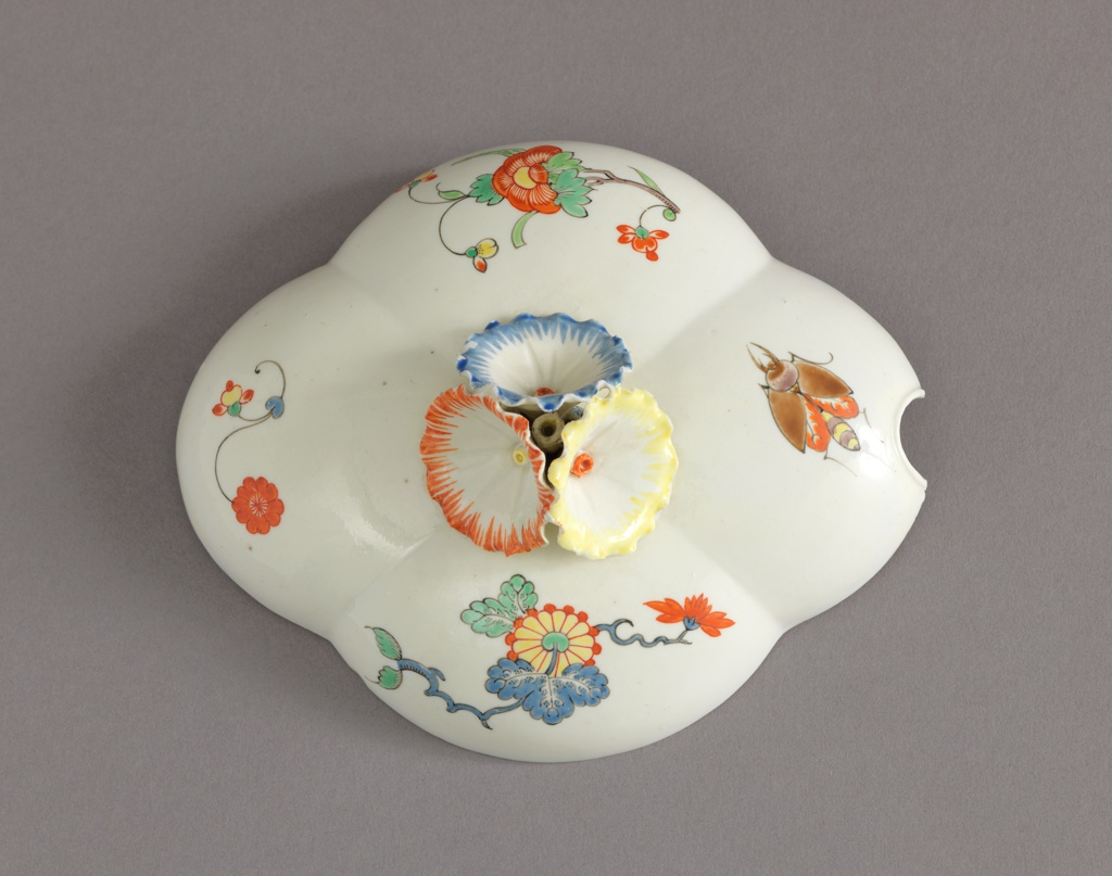 """Four-lobed, decorated with insects and branches of blossoms in the """"Korean"""" style.  Rim of tray decorated with brown band. Cover with handle of three petunia-like flowers, and notched for ladle."""