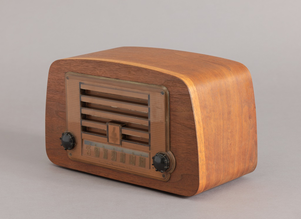 Rectangular bentwood case with curved sides and top; horizontal speaker grille in front, above station tuner flanked by two black plastic control knobs.
