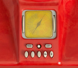 Molded red Bakelite housing with angled and contoured top having projecting, pierced circular speaker surmounting square station dial with long needle indictator in center, and white control buttons below.