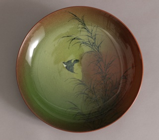 An orange and red toned circular plate with a thin branch in the foreground and a brown and white bird flying behind it. Reverse: solid red-brown glaze.