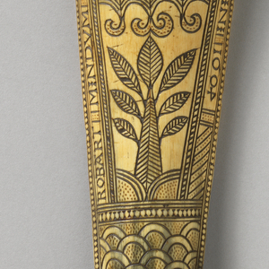 """Typical curved tapered cylindrical shape, upcurved at both ends, with engraved and stained decoration featuring a fleur-de-lys over a band of guilloché above a stylized flower-foliage cluster and arched pattern all surrounded by the inscription """"Robert Mindum made this shooing...(worn at top) s Gamlet Anno domini 1604""""."""