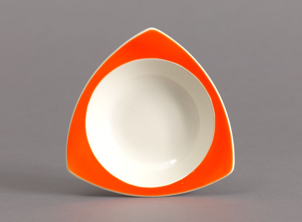Small triangular bowl with curved red rim and circular white well.