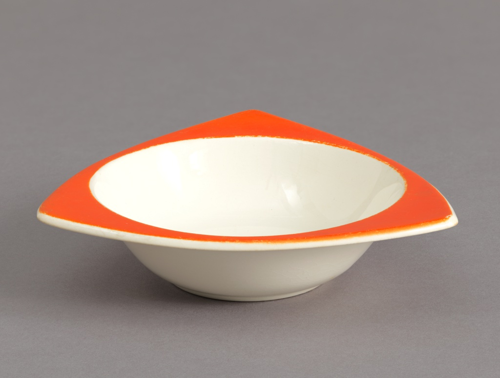 Circular bowl having white interior and red triangular rim wth curved edges.