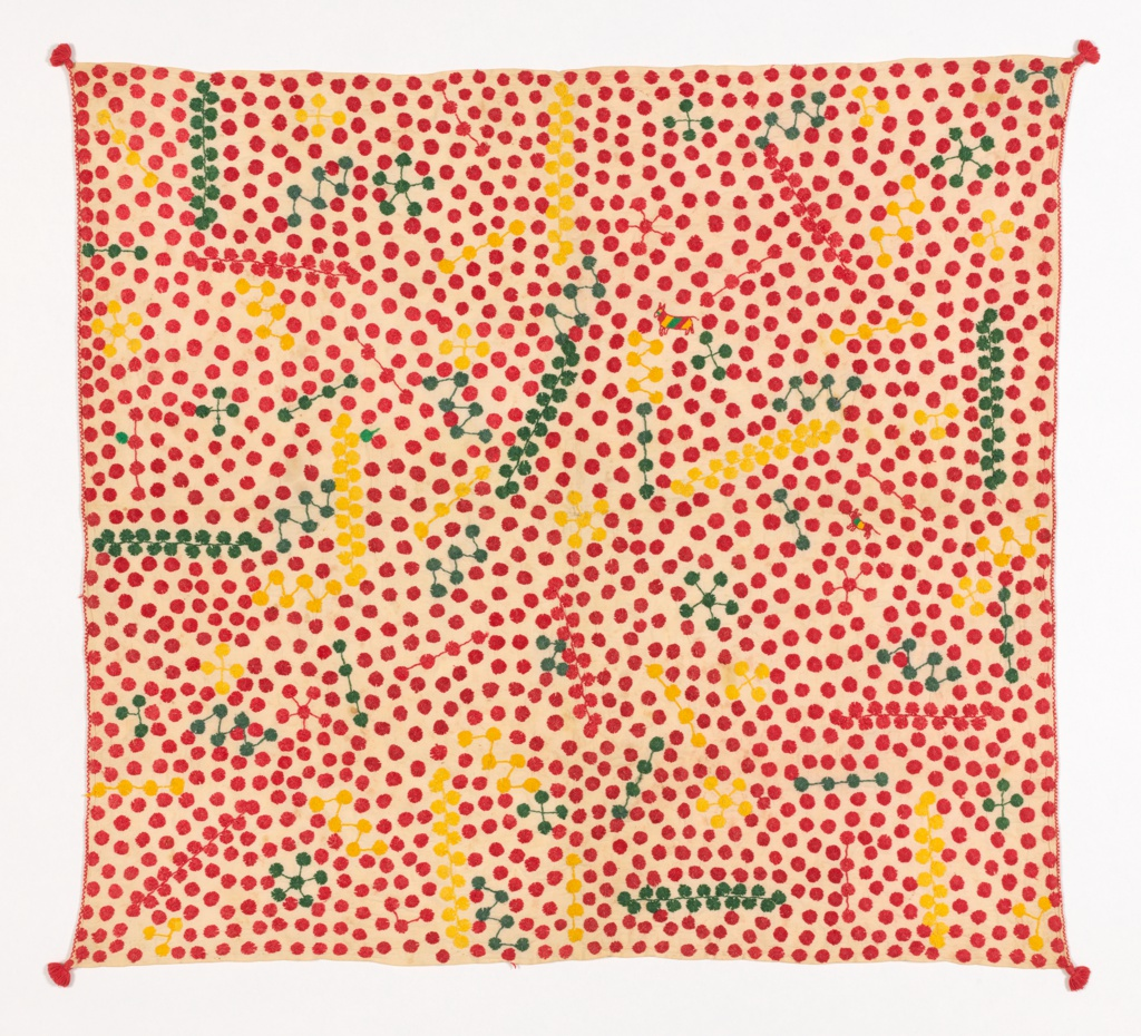 Carrying cloth (servilleta) of white cotton plain weave embroidered in bright red, yellow, and green in all-over pattern of dime-sized dots, some connected by lines to form stars, bands, or constellations, in a random design. One small striped bull, off center. Embroidery is in a long stitch radiating from a central point and is reversible. Small red tassels at corners.