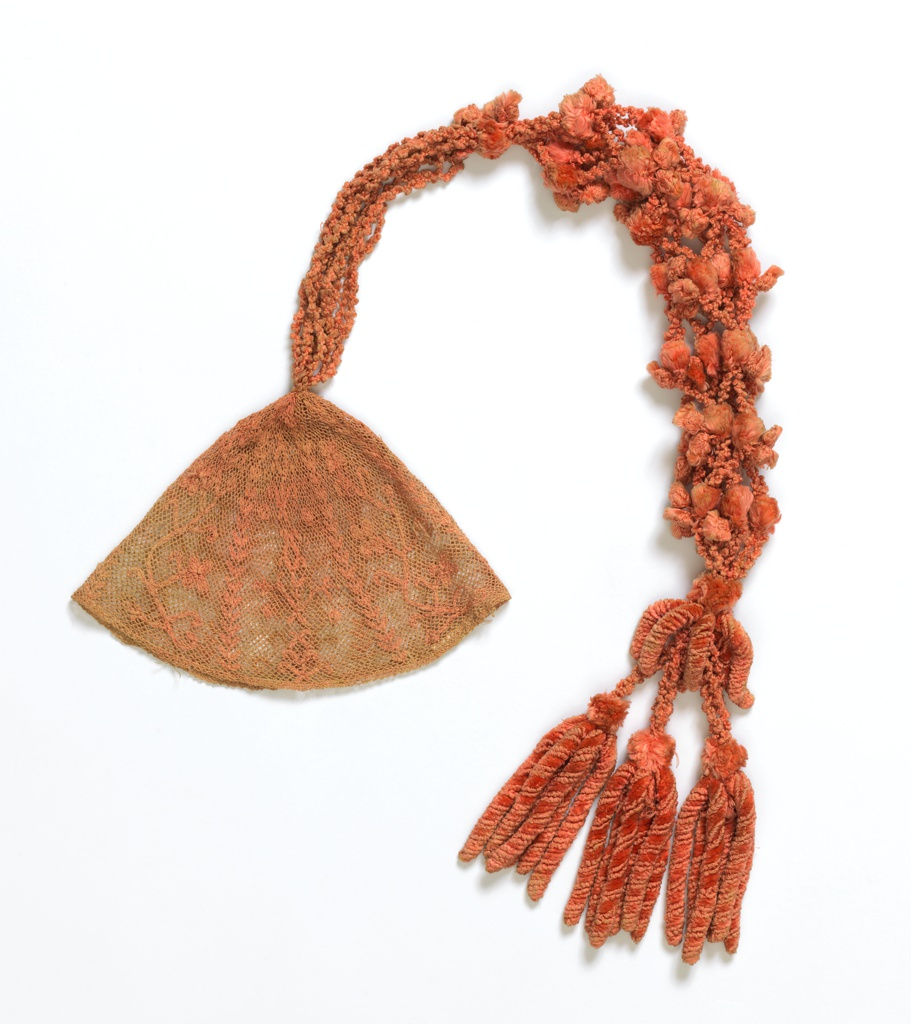 Close fitting skull cap of pink silk net. Embroidered in pink silks. Very long elaborate tassel of strands of chenille in coral pink, made into a group of strands.