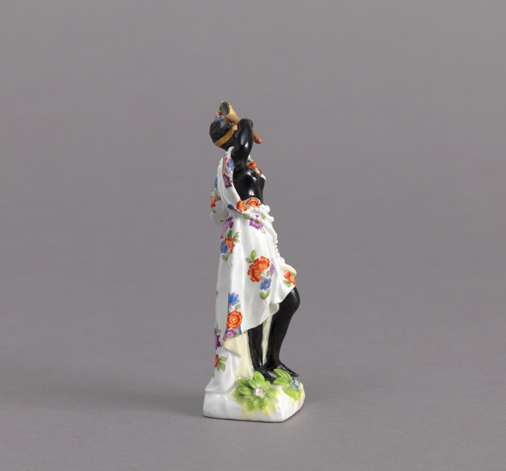 Standing female figure, black, wearing flowered skirt and cape and feather headdress, holding a stick.