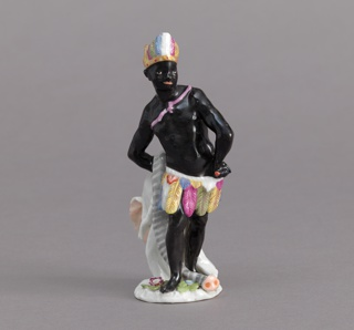 Standing black figure, wearing feather skirt and headdress, an elephant skin over right arm.  Based on an 18th century model.