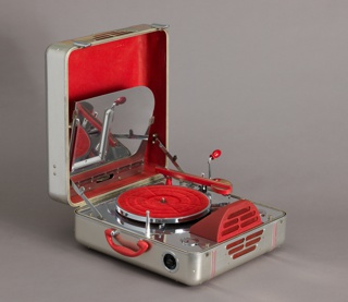 Portable phonograph in square aluminum case with rounded edges and corners; red plastic handle and control dials; one side with pierced slits for speaker. Bottom of case contains metal deck with red turntable, needle arm, domed speaker and controls. Lid with file holder with sheet metal dividers to house records.