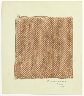 Woven sample mounted to a cardboard card with notations by the designer. Weft is light brown three-ply yarn alternating with flat metallic copper strip paired with wrapped metallic gold yarn. Selvedge at right.