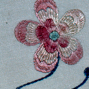 """Stem with two blossoms in muted colors within a notched circle. The initial """"D"""" appears in the center of a wheel-like shape."""