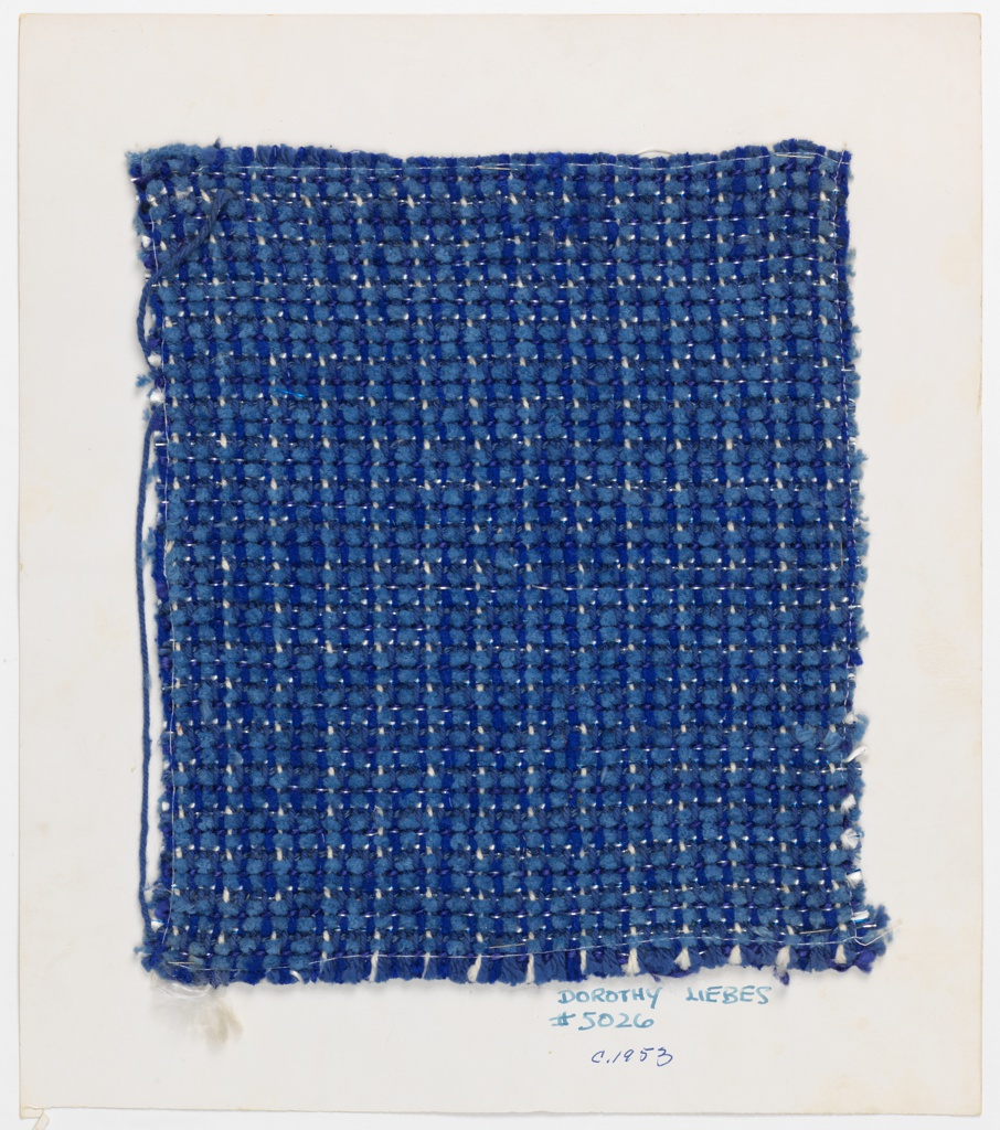 Plain weave in shades of blue and every eighth warp in white. Weft has two shots over two under two alternating two shots over one under one. Blue chenille, two shades of blue smooth yarn and white yarn. Many rows paired with silver flat metal.