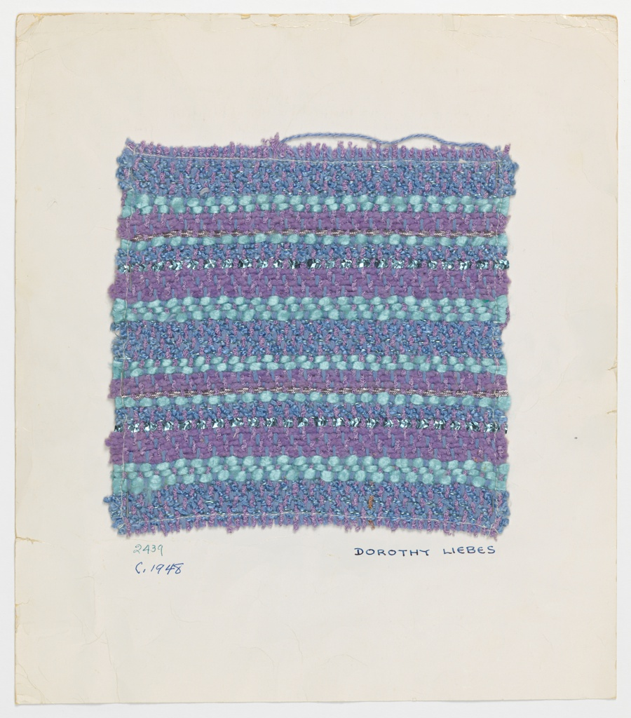 Twill variation in shades of blue and light purple. Warp has alternate light purple boucle yarns and light blue two-ply yarn. Weft has a band sequence of eight boucle cotton with narrow metallic yarn, three light blue synthetic, five light purple chenille, one metallic braid, three blue boucle with narrow metal yarn, one blue synthetic, one flat braided metallic yarn, three purple chenille, and two blue synthetic. The sequence repeats for a pattern unit. Some bands are 2/2 twill and some are 3/1 twill.