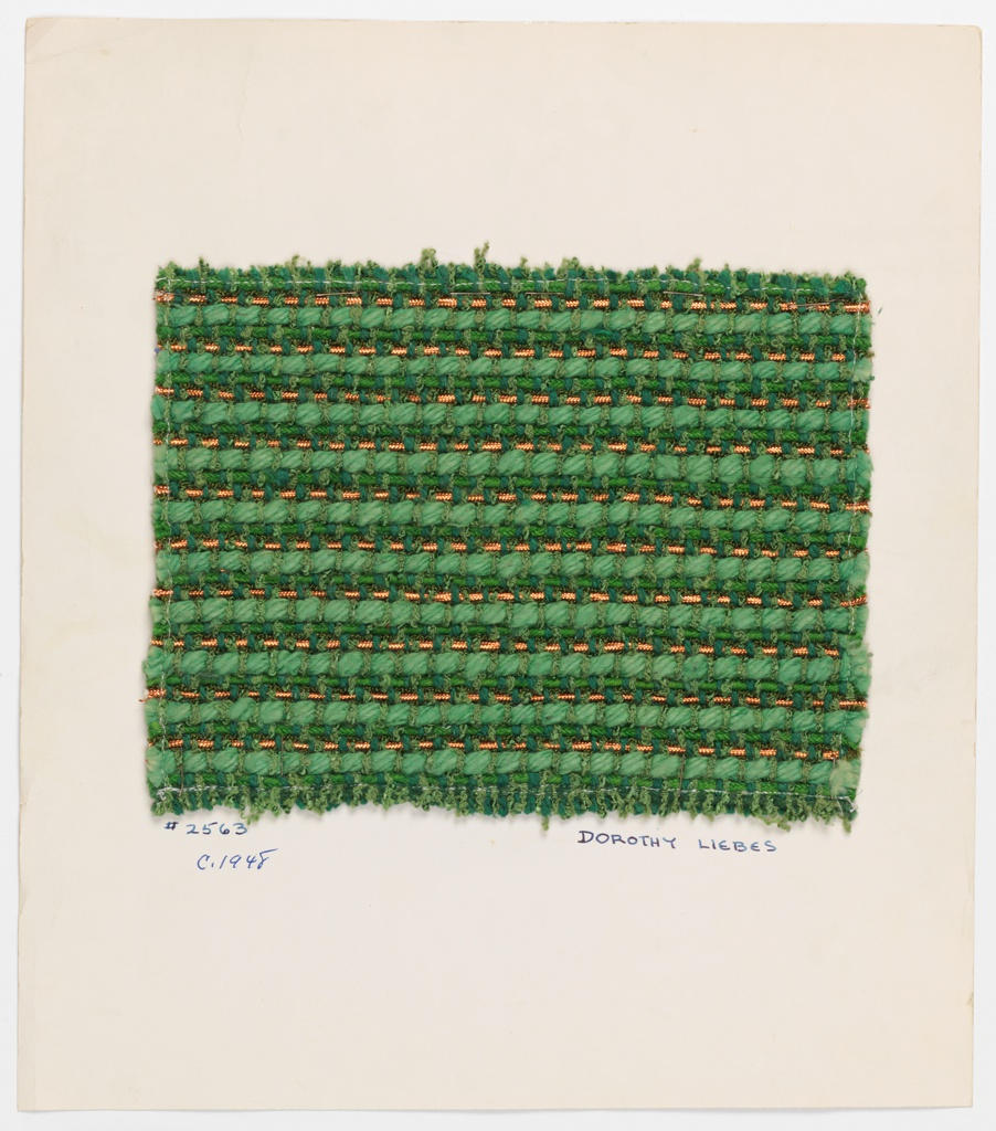 Woven sample mounted to a cardboard card with notations by the designer. Green with horizontal whales and metallic effects. Warp is paired green bouclé and smooth yarns. Weft is a repeating sequence of green bouclé, wrapped-core copper metallic yarn, green bouclé, braided green yarn and thick plied green yarn.