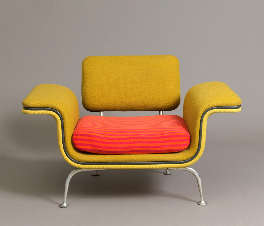 Low rectilinear form, the seat/arms and rectangular back upholstered in yellow-green; form trimmed with strip of khaki green vinyl welting running horizontally through center; removeable rectangular seat cushion upholstered in orange and pink striped woven textile; cast tubular aluminum posts support back; four short splayed cast tubular aluminum legs with circular pad feet.