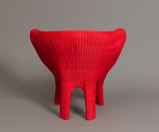 Woven red Apui fibers around black plastic chair.
