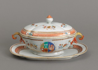 A tureen, lid and stand decorated in gilt with red details. Depicted on the set are small flowers and an emblem with a chicken, lobster, and other items.
