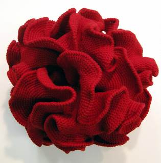 Model of hyperbolic space crocheted in bright red wool. Spherical form with crenellated surface.