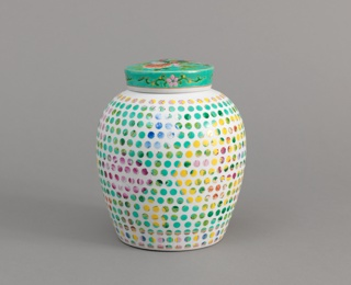 Ovoid vessel showing sandblasted surface featuring dotted geometric pattern, with cover showing original glazed floral decoration.
