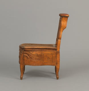 a) Carved fruitwood bidet with caned back, four cabriole legs, back ones having rocaille ornament at foot, front ones with small scrolls at foot; leather covered hinged lid at top of back support concealing three compartments. b) hinged, double caned seat concealing (c) removable faience bowl with blue floral sprays and border on blue-white glaze.