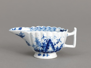 Creamboat with high foot and scalloped edges. Chinoiserie cobalt decoration .