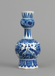 Eight-sided bulbous body on tall flaring base, tapering neck with bulbous knop and flared mouth; painted in underglaze blue on white, on the base with lambrequin border, on body with peacock, rocks, flowers, insects, lambrequin border, on neck and mouth with leaf borders and floral scrolls.