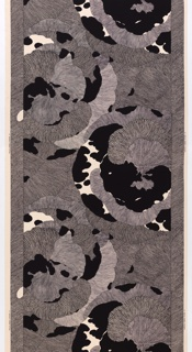 Floral shapes with each petal decorated differently. Width of patternis 133.5cm (52 1/2in.) with a margin at each side. Black on off-white.