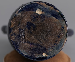 Thrown, thin-walled body of attenuated ovoid form with double neck rising from shoulder; double mouth with ruffled and crumpled edges; two applied double-loop handles on left and right; low, spreading circular foot; the whole covered in dark blue glaze, portions mottled in shades of purple and green silver metallic blotches in slight relief.