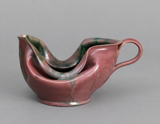 Thrown red earthenware body with slumped, deeply folded sides, short spout, applied curved handle, and low foot. Exterior covered with variegated rose-colored glaze, with streaks of brilliant green glaze. Interior glazed in mottled dark green with areas of lusterless and high luster glaze. Underside partially glazed.