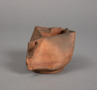 Pitcher or sauceboat of thin-walled, irregular form with flat circular base; sides  pinched together at one side to form handle; opposite side pinched to create trilobe spout and lip. Unglazed; fired unevenly, creating pale/dark spots over surface.