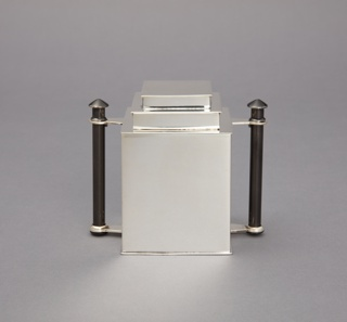 Boxy sugar bowl with stepped lid, making form reminiscent of a skyscraper; vertical, black cylindrical handle on either side; polished surface.