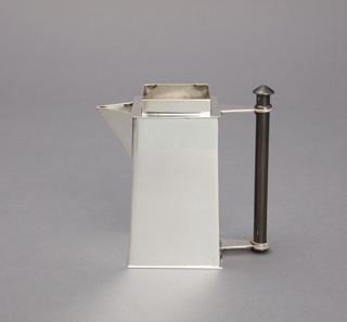 Boxy form reminiscent of a skyscraper; vertical, black cylindrical handle; triangular spout; polished surface.