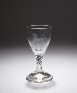 Wineglass with ovoid bowl on a short stem. Light conical foot. The base of the bowl and the stem are cut in lozenge-shaped facets.  On the bowl a diamond stipple engraving of a galloping horse in a wooded, grassy landscape.
