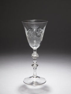 """Wine glass with a  rounded funnel bowl. The remarkably narrow stem consists of a baluster knob with two rows of inserted air bubbles, underneath which is a small flattened knob, a straight part and a swelling with inserted air drop. Conical foot.   On the bowl hanging from a crown are the coats of arms of William V and his wife Princess Wilhelmina of Prussia. Around the coat of arms of William a stylized garter with his motto: HONI SOIT QUI MALY PENSE (""""Shame on anyone who thinks evil of it""""). The coats of arms are held by two wild roaring lions, one laying and one standing. Underneath very fine engraved clouds."""